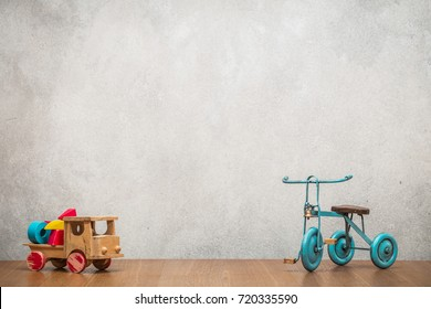 Retro old toy tricycle and obsolete wooden truck with construction blocks front concrete textured wall background. Vintage instagram style filtered photo