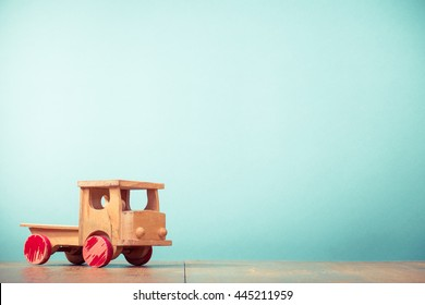 Retro old toy wooden truck front aquamarine background. Vintage instagram style filtered photo