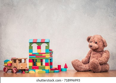 Retro old toys: Teddy Bear, wooden house made of construction blocks and truck front concrete textured wall background. Vintage instagram style filtered photography