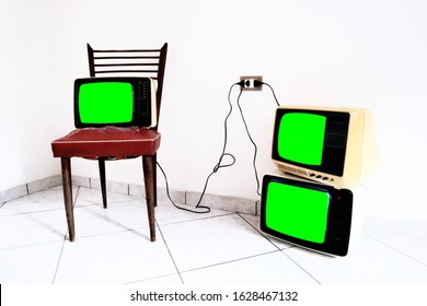 Retro old TV on the vintage chair and plug plugged into the power line. TV with frame screen isolate on Green Chroma Key