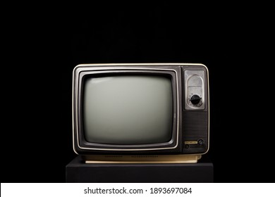 Retro old TV on wooden box on black background