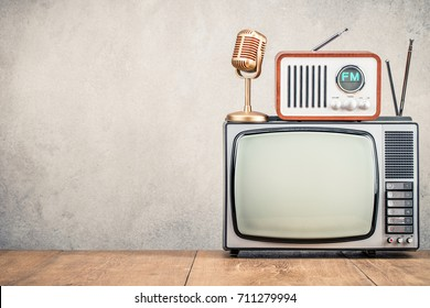 Retro old TV set, FM radio receiver and golden microphone front concrete wall background. Broadcasting concept. Vintage instagram style filtered photo