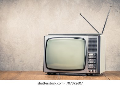 Retro old TV set receiver on table front textured concrete wall background. Television broadcasting concept. Vintage instagram style filtered photo