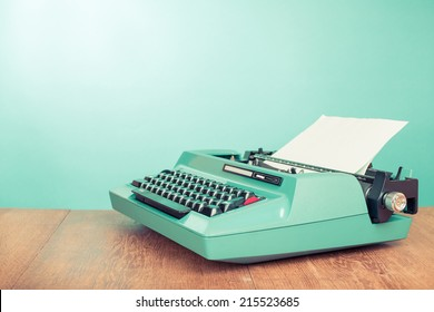 Retro old typewriter with paper on wooden table front mint green background