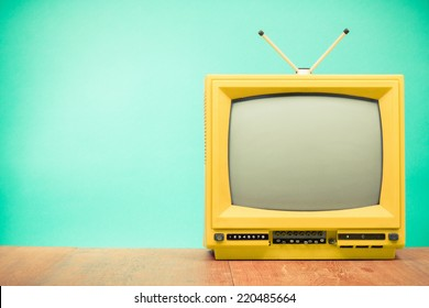 Retro old yellow TV front turquoise wall background