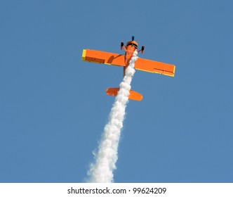 retro orange colored airplane performing aerobatics