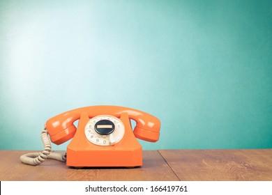 Retro orange telephone on wood table near aquamarine wall background