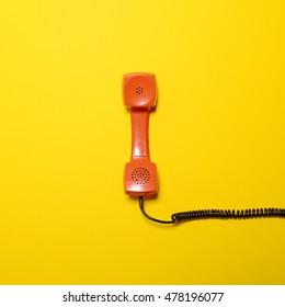 Retro orange telephone tube on yellow background - Flat lay