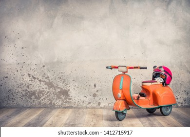 Retro orange toy aged rusty children's pedal scooter from 60s and red helmet with aviator goggles front loft textured concrete wall background. Kids racing concept. Vintage old style filtered photo