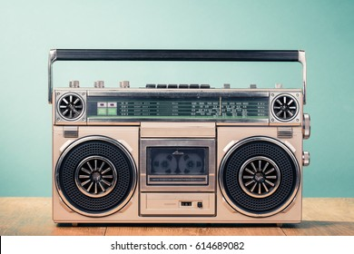 Retro outdated cassette tape recorder from 80s on table front mint green background. Vintage old style filtered photo