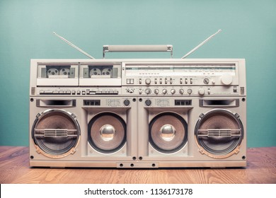 Retro outdated portable stereo boombox radio receiver with cassette recorder from circa 80s front mint green wall background. Listening music concept. Vintage old style filtered photo