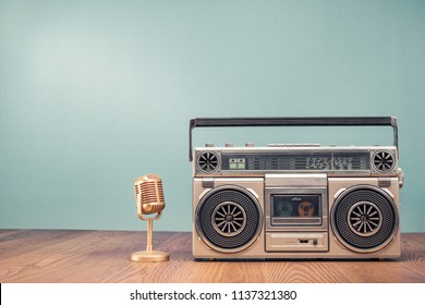 Retro outdated portable stereo boombox radio receiver with cassette recorder from circa 80s and golden mic front mint green wall background. Recording music concept. Vintage old style filtered photo