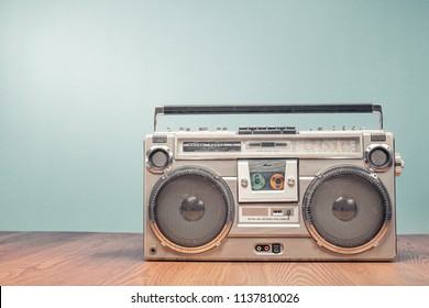 Retro outdated portable stereo boombox radio receiver with cassette recorder from circa late 70s front mint green wall background. Listening music concept. Vintage old style filtered photo