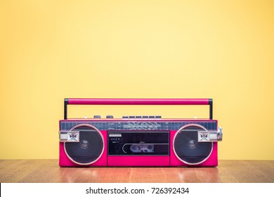 Retro outdated red portable stereo radio cassette recorder from 80s front yellow background. Vintage old instagram style filtered photo