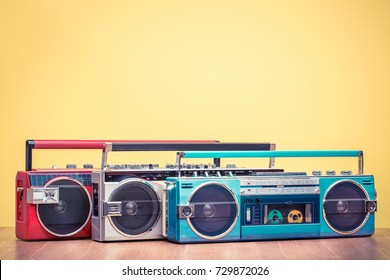 Retro outdated red portable stereo radio cassette recorder from 80s front yellow background. Vintage instagram old style filtered photo