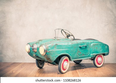 Retro outdated rusty metal turquoise pedal car toy from circa late 60s or early 70s in front concrete textured wall background. Vintage style filtered photo