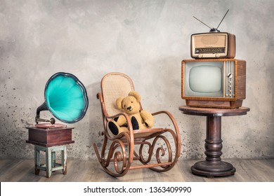 Retro outdated television, broadcast radio from circa 50s on wooden table,  old phonograph, Teddy Bear toy sitting on aged rocking chair front concrete wall background. Vintage style filtered photo