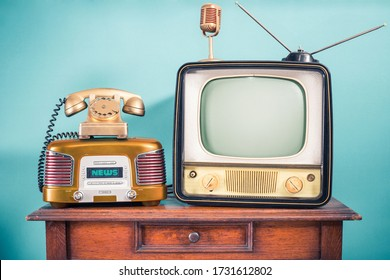 Retro outdated TV set from 60s, old FM radio, golden microphone and classic telephone on oak wooden table front mint blue background. News, journalism nostalgia concept. Vintage style filtered photo
