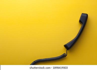 Retro phone handset on yellow background. Copy space.