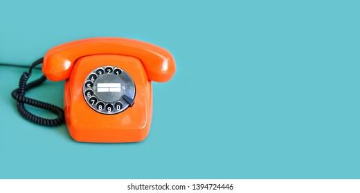 Retro phone orange color, vintage handset receiver on green background. copy space