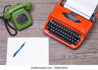 Retro phone and typewriter on a wooden table with top view