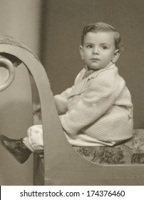 Retro photo of a baby sitting on a chair