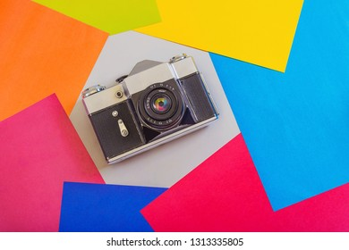 Retro photo camera on a colored background. The concept of vivid memories.