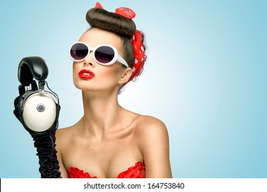 The retro photo of a cute pin-up girl in sunglasses with vintage music headphones.