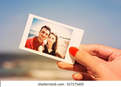 Retro Photo Of Girl Hand Holding Instant Photo Of Happy Couple On Beach