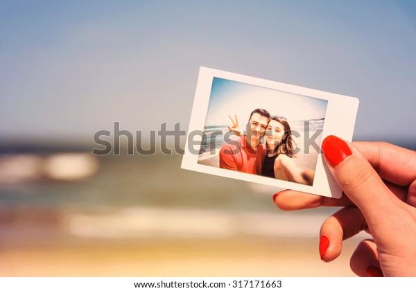 Retro Photo Of Girl Hand Holding Instant Photo Of Happy Couple On Beach
