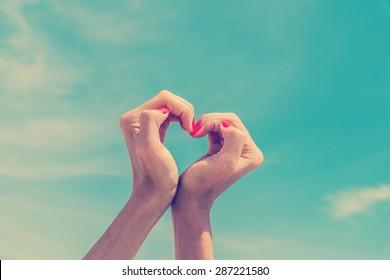 Retro Photo Of Girl Hands In Heart Shape On Blue Sky