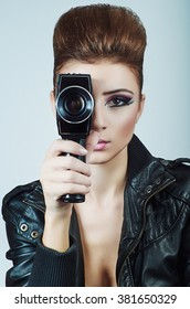 Retro photo of a glamorous girl with an old vintage cinema 8 mm camera, looking like a sexy producer, shooting a movie on blue background.