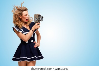 Retro photo of a glamorous pin-up sailor girl with an old vintage cinema 8 mm camera shooting a movie on blue background.