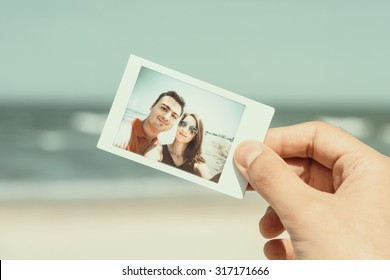 Retro Photo Of Man Hand Holding Instant Photo Of Happy Couple On Beach