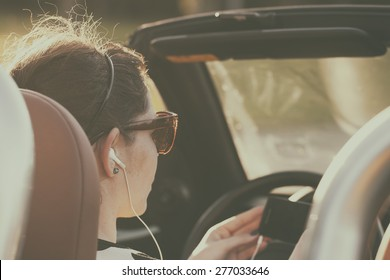 Retro photo of woman listening music in car while driving