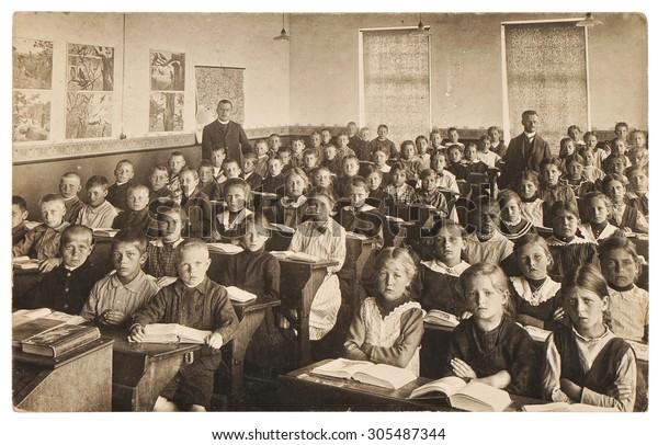 Retro-Bild der Klassenkameraden. Gruppe von Kindern im Klassenzimmer. Vintage Foto aus dem Jahr 1920 mit Original-Filmkorn, Unschärfe und Kratzer.