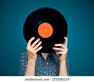 Retro picture of woman with red nails holding vinyl record on dark blue background