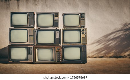 Retro of pile old television on floor in front of old wall background. , vintage TV style photo