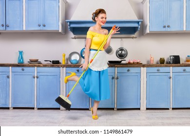 Retro / pin up girl female woman / housewife wearing colorful top, skirt and white apron holding mop and cleaning washing floor in the kitchen with blue cabinets and utensils. Housework concept