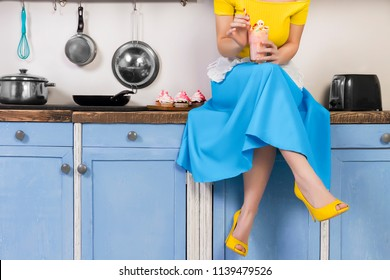Retro pin up girl woman female housewife wearing colorful top, skirt and white apron holding cooked sweet strawberry milkshake sitting in the kitchen with utensils and tray with cupcakes.