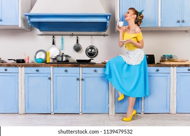 Retro pin up girl woman female housewife wearing colorful top, skirt and white apron holding and drinking cup of coffee sitting in the kitchen with utensils and tray with cupcakes and milkshake.