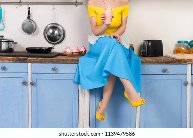 Retro pin up girl woman female housewife wearing colorful top, skirt and white apron holding cooked sweet strawberry milkshake sitting in the kitchen with utensils and tray with cupcakes. Retro styled