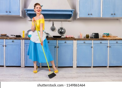 Retro / pin up girl woman female / housewife wearing colorful top, skirt and white apron holding mop and cleaning washing floor in the kitchen with blue cabinets and utensils. Housework concept