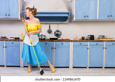 Retro pin up girl woman female / housewife wearing colorful top, skirt and white apron holding mop singing and cleaning washing floor in the kitchen with blue cabinets and utensils. Housework concept