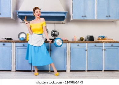 Retro pin up girl woman female housewife wearing colorful top, skirt and white apron and yellow high heels holdingwooden spoons and pan standing in the blue kitchen with blue cabinets and utensils.
