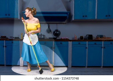 Retro pin up girl woman female housewife wearing yellow top, blue skirt and white apron holding mop singing and cleaning floor in stage light kitchen with blue cabinets and utensils. Housework concept