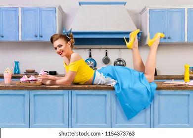 Retro pin up girl woman female housewife wearing yellow top, blue skirt and white apron lying relaxing on kitchen with utensils and tray with sweet strawberry milkshake and cupcakes. Retro styled