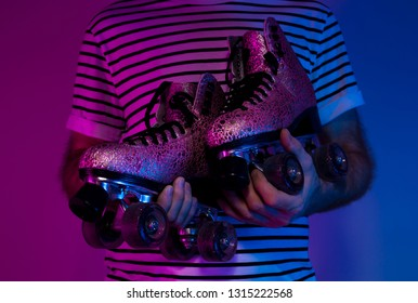 Retro pink glittery roller skates in man's hands. Colorful (purple and blue tonal transitions) background. Dark moody light.