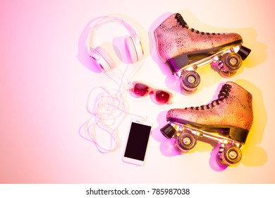 Retro pink glittery roller skates, mobile phone (smartphone), headphones and sunglasses captured from above (top view, flat lay). Fun, recreation and active lifestyle - background (free text space).