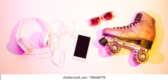 Retro pink glittery roller skates, mobile phone (smartphone), headphones and sunglasses captured from above (top view, flat lay). Fun, recreation and active lifestyle - banner layout.